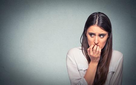 Jonge aarzelend nerveuze vrouw haar nagels bijten iets of angstig, geïsoleerd op grijze muur achtergrond met kopie ruimte verlangen. Negatieve menselijke emoties gezichtsuitdrukking gevoel