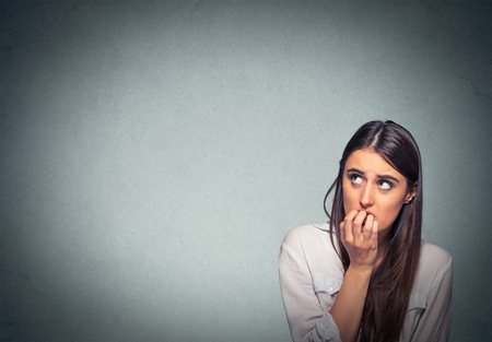 hesitant: Young hesitant nervous woman biting her fingernails craving something or anxious, isolated on gray wall background with copy space. Negative human emotions facial expression feeling