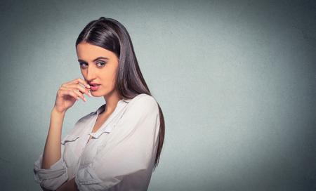 astuto, astuto, mujer joven intrigante trazado algo aislado en el fondo gris. Negativo emoción humana sensación de la expresión facial Foto de archivo