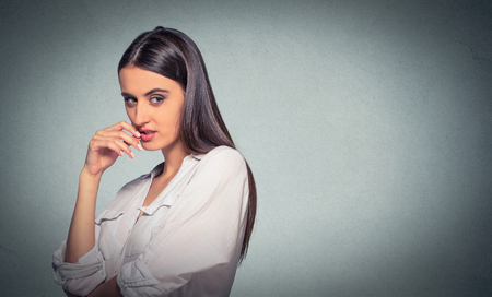 sneaky, sly, scheming young woman plotting something isolated on gray background. Negative human emotion facial expression feeling Stock Photo