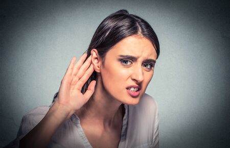 Closeup portrait young nosy woman hand to ear gesture trying carefully listens in on juicy gossip conversation isolated gray background. Human face expression. Hard to hear