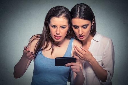 최신 가십 뉴스를 논의 휴대 전화를 찾고 두 놀란 소녀는, 그들이 고립 된 회색 배경 참조 무엇을 깜짝 놀라게