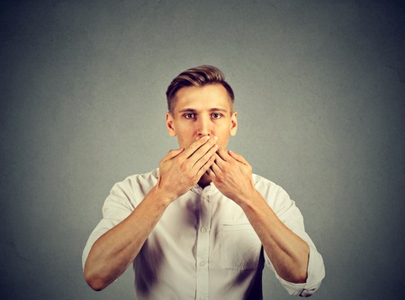 perturbed: man with hands over his mouth, speechless isolated on gray wall background