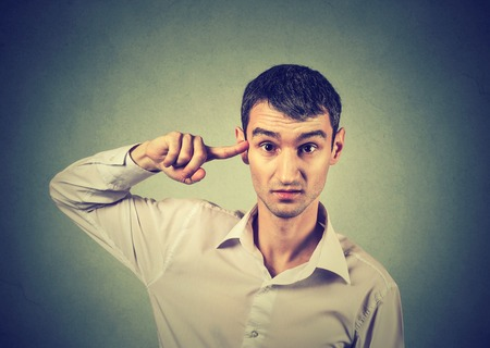 expresion corporal: joven enojado enojado haciendo un gesto con el dedo contra el templo de venta ¿estás loco? Aislado en el fondo gris. La emoción negativa expresión facial lenguaje corporal sensación Foto de archivo