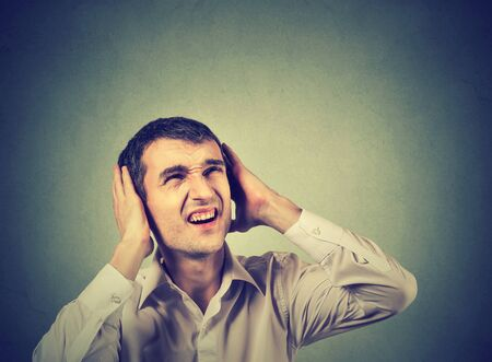 decibel: Young annoyed, unhappy, stressed man covering his ears, looking up, stop making loud noise, giving me headache isolated on gray background. Negative emotion reaction Stock Photo