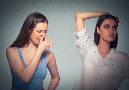 stinks: two women, one pinching nose something stinks, girls underarm isolated gray background