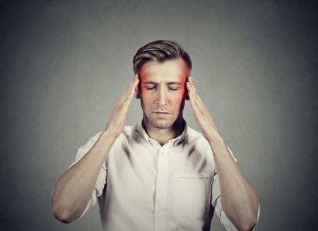 Man with headache thinking very intensely concentrating isolated on gray wall background Stock Photo