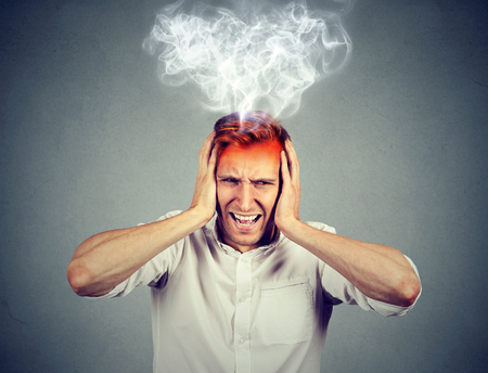 burn: Portrait young stressed man screaming frustrated overwhelmed steam coming out up of head isolated on grey wall background. Negative human face expression emotion feelings perception