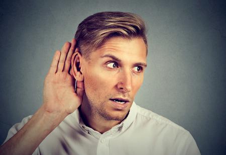 회색 배경에 고립 된 대화 뉴스 도청을 듣고 호기심 남자. 인간의 얼굴 표정, 반응, 감정, 삶의 인식 스톡 콘텐츠