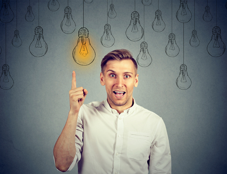 happy young man pointing at light bulb has a solution