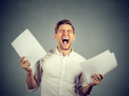 unhappy man: Angry stressed screaming business man with documents papers paperwork isolated on gray wall background. Negative emotions face expression Stock Photo
