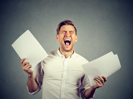 factura: Tensionado enojado gritando hombre de negocios con los documentos papeleo papeles aislados sobre fondo gris de la pared. Las emociones negativas se enfrentan a la expresión