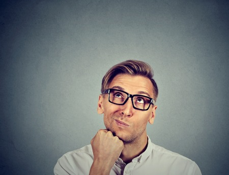 business skeptical: confused skeptical man thinking looking up isolated on gray background with copy space above head. Human face expressions, emotions, feelings, body language