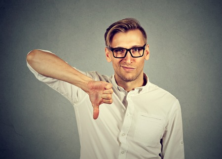 angry, unhappy, young man showing thumbs down sign, in disapproval of offer isolated on gray background. Negative human emotion facial expression feelings Stock Photo