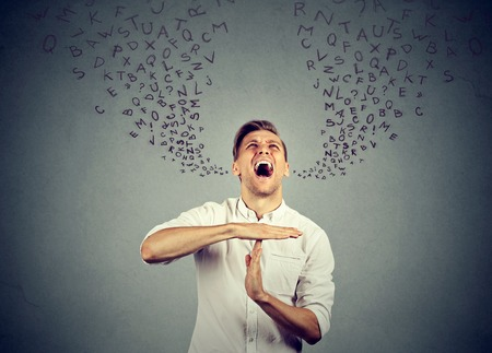 foreign bodies: Young man showing time out hand gesture, frustrated screaming to stop alphabet letters coming out of mouth isolated on gray background. Human emotions face expression reaction