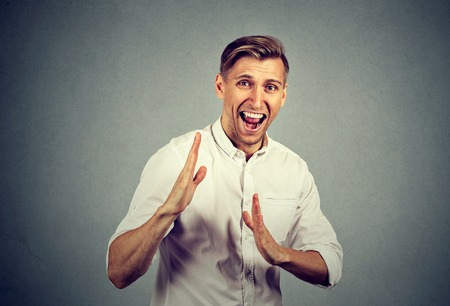 negative emotion: angry mad, furious man raising hands in  air attack with karate chop isolated gray background. Negative emotion facial expression feeling body language