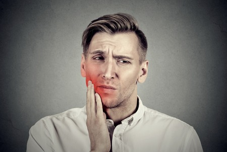 amalgam: Closeup portrait young man with sensitive toothache crown problem about to cry from pain touching outside mouth with hand isolated on gray background. Negative human emotion face expression feeling Stock Photo