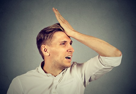gaffe: Regrets wrong doing. Closeup portrait silly young man, slapping hand on head having a duh moment isolated on gray background. Negative human emotion facial expression feeling, body language, reaction