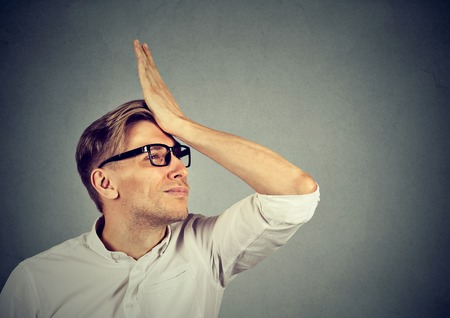 gaffe: Regrets wrong doing. Silly young man, slapping hand on head having a duh moment isolated on gray background. Negative human emotion facial expression feeling, body language, reaction