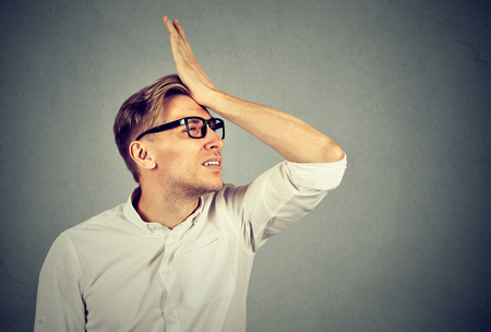 Regrets wrong doing. Silly young man in glasses slapping hand on head having a duh moment. Negative human emotion facial expression feeling, reaction Stock Photo