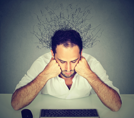 ocd: Sad young man with worried stressed face expression and brain melting into many lines question marks sitting at table looking at computer keyboard. Adhd anxiety disorders
