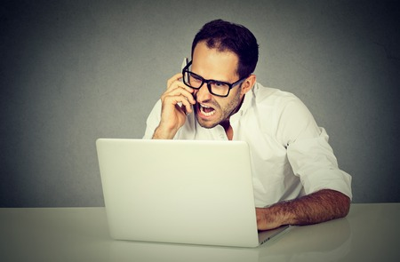Hombre joven frustrado y enojado de compras en línea que grita en un teléfono. emociones humanas negativas frente a la expresión