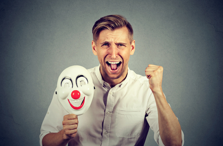 formalities: Portrait young upset angry screaming man holding a clown mask expressing cheerfulness happiness isolated on gray wall background. Human emotions feelings