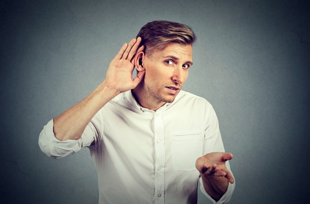 Unhappy hard of hearing man placing hand on ear asking someone to speak up or listening to bad news, isolated on gray background. Negative emotion facial expression feelings.