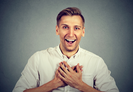 feeling happy: Happy young handsome man looking shocked surprised laughing hands on chest open mouth, isolated on gray background. Positive human emotion facial expression feeling Stock Photo
