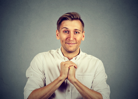 human kind: Kind young man showing clasped hands, pretty please isolated on gray background. Human emotion facial expression feelings, body language