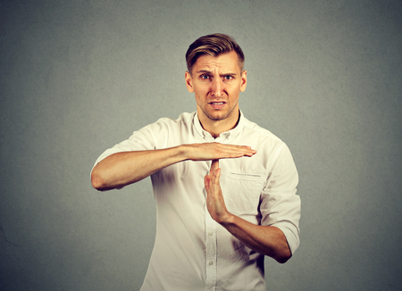 Young angry man showing time out hand gesture isolated on grey wall background. Human emotions face expression reaction