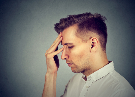 suicidal: Side profile headshot sad depressed, alone, disappointed gloomy man resting head on hand having suicidal thoughts isolated gray background. Human emotion facial expression