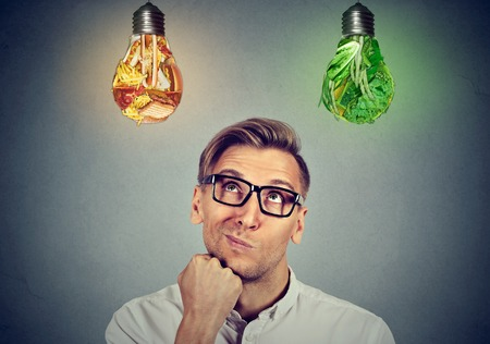vision loss: Man in glasses thinking looking up at vegetables light bulbs craving junk food isolated on gray background. Diet choice right nutrition healthy lifestyle concept Stock Photo