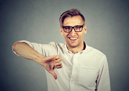 desprecio: hombre joven que muestra los pulgares abajo firma sarcásticos gesto de la mano, alguien hizo feliz error, perdido, no aislados sobre fondo gris. las emociones humanas, la expresión facial, la actitud de los sentimientos Foto de archivo