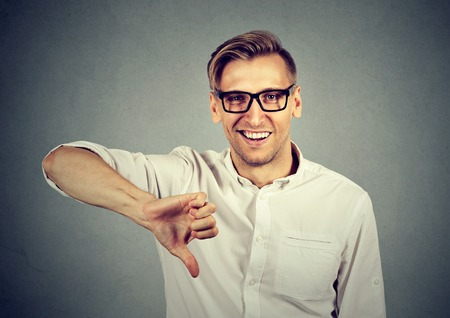 sarcastic: sarcastic young man showing thumbs down sign hand gesture, happy someone made mistake, lost, failed isolated on gray background. Human emotion, facial expression, feelings attitude