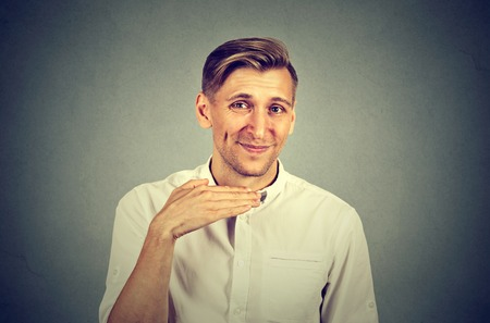 admonish: angry young man gesturing with hand to stop talking, cut it out isolated on gray background. Negative emotion, facial expressions, feelings
