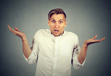 ambiguous: Ignorance and arrogance. Closeup portrait young man shrugging shoulders who cares so what I dont know gesture isolated on gray wall background. Human body language. Whatever attitude reaction