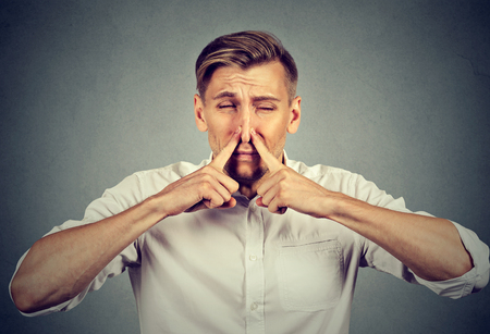 pinches: man pinches nose with fingers looks with disgust something stinks bad smell isolated on gray background. Human face expression body language reaction