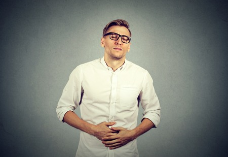 irritable bowel syndrome: Young man with stomach pain indigestion