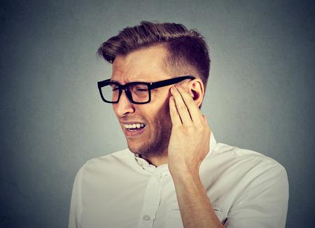 이명. 근접 촬영 측면 프로필 아픈 젊은 남자 회색 배경에 고립 된 그의 고통스러운 머리를 만지고 귀 통증 데