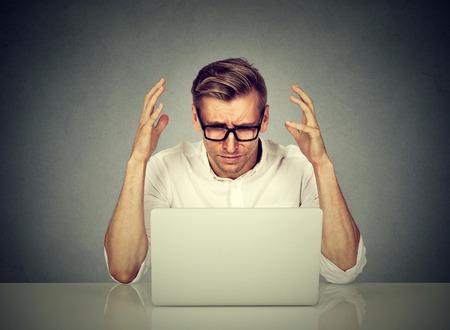 Betont Mann arbeitet am Computer. Negative menschliche Emotionen Gesichtsausdruck