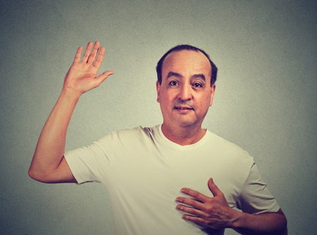 testify: Middle aged man making a promise isolated on gray wall background Stock Photo