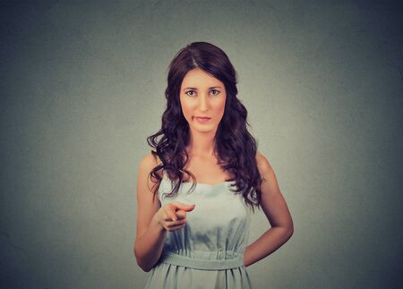 strict: angry displeased young woman pointing at camera isolated on gray background Stock Photo