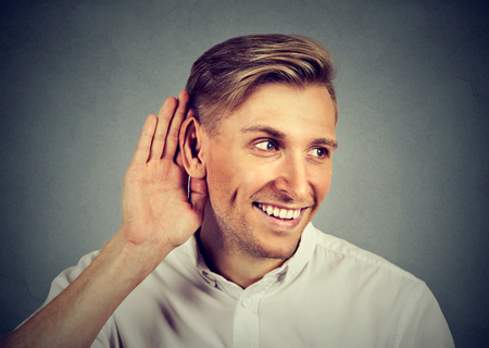 handsome young nosy business man secretly listening in on conversation, hand to ear, smiling at gossip, isolated on gray background. Privacy curiosity concept Stock Photo