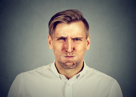 detestable: angry young man, about to have nervous breakdown, isolated on gray wall background. Negative human emotions facial expression feelings attitude