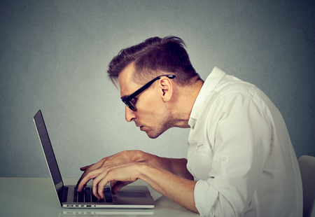 ergonomics: Side profile young man in glasses working on computer sitting at desk isolated on gray wall office background. Long monotonous tiresome working hours life concept