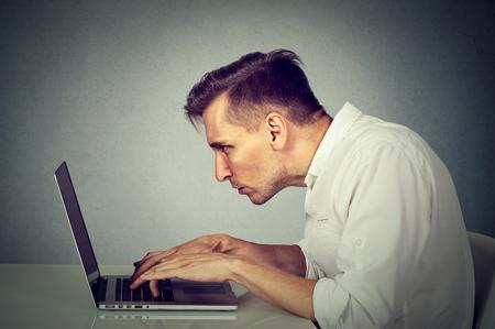 側プロファイルの若い男は、灰色の壁オフィス背景で隔離の机に座ってコンピューター上で作業します。長い単調な退屈な作業時間の生活の概念