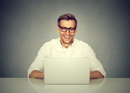 man working computer: Young happy business man working in office, sitting at desk, looking at laptop computer screen, smiling
