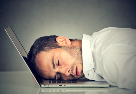 burdensome: Business man sleeping on his laptop in his office