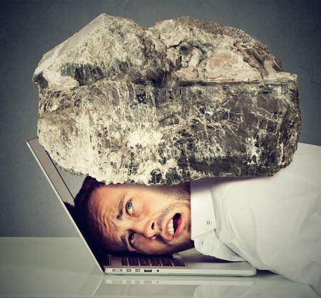 burdensome: Young desperate business man with his head squeezed between laptop keyboard and  rock